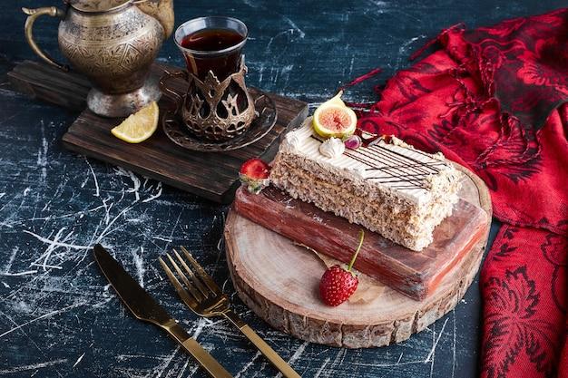 Een plakje cake met een glas thee op een houten bord.