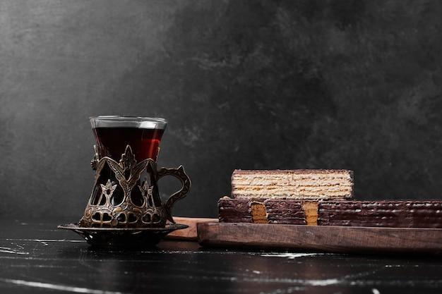 Een plakje cake met een glas thee.