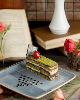 Een plakje cake met gehakte pistache en kersenbes.