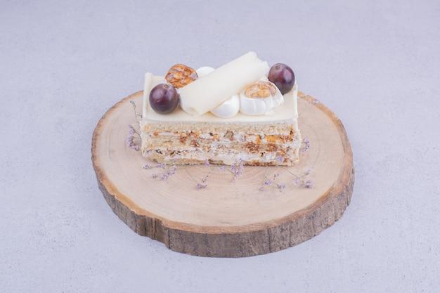 Een plakje cake met walnoot en druiven op een houten bord.