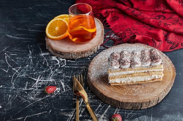 Een plakje cake op een houten bord, bovenaanzicht.
