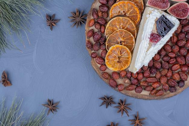 Een plakje cheesecake in een fruitschaal met vijgen, stukjes sinaasappel en heupen