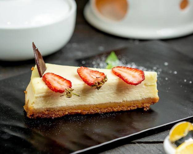 Een plakje cheesecake met aardbeiplakken