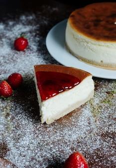 Een plakje cheesecake met karamel-aardbeiensiroop bovenop.