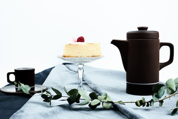 Een plakje cheesecake met koffieset.