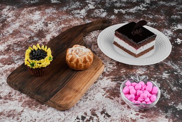 Een plakje chocolade cheesecake in een witte plaat met cupcakes.