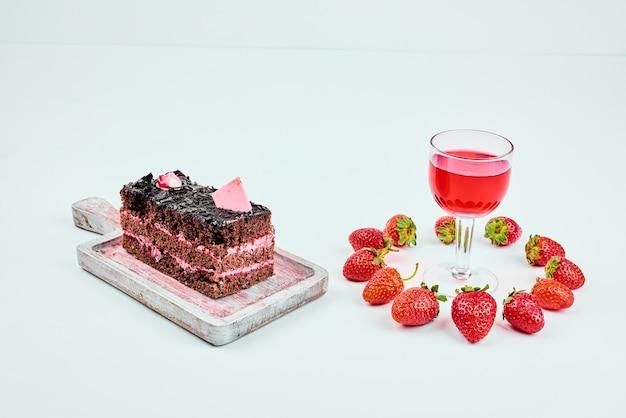 Een plakje chocolade cheesecake met rode drank.