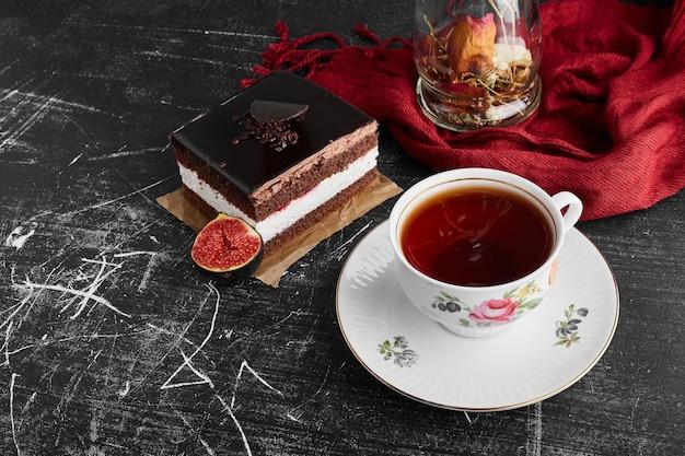Een plakje chocolade cheesecake op een zwarte ondergrond met vijgen en een kopje thee.