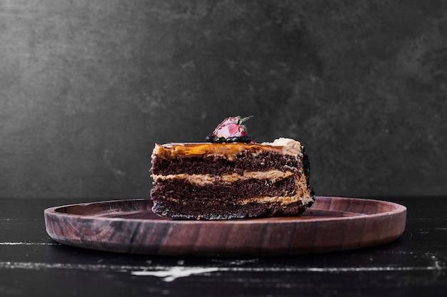 Een plakje chocoladekaramelcake in een houten plaat.