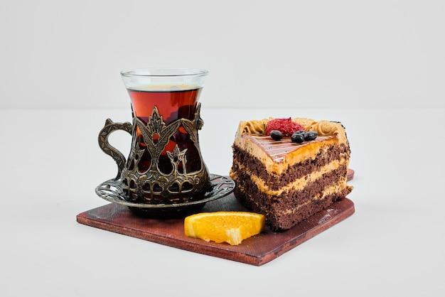 Een plakje chocoladekaramelcake met een glas thee.
