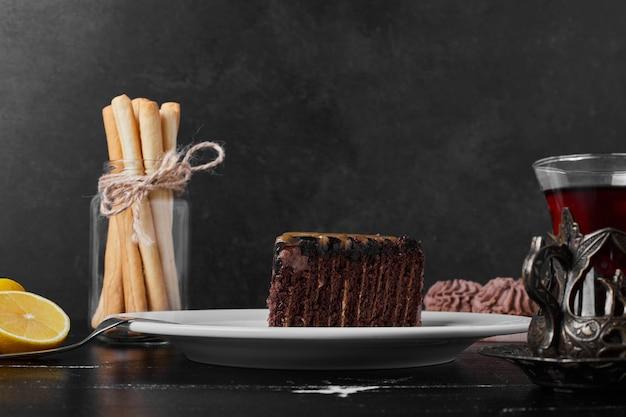 Een plakje chocoladetaart in een witte plaat met een glas thee.