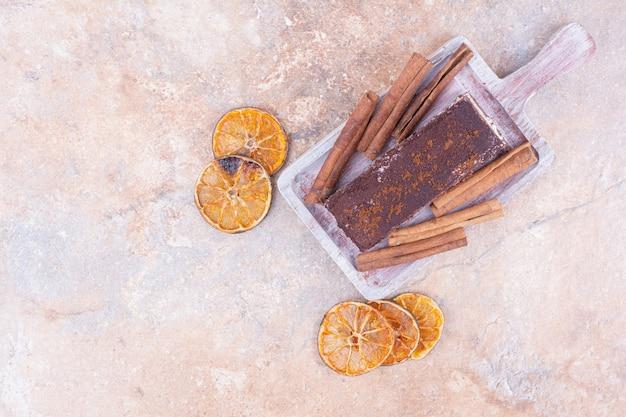 Een plakje chocoladetaart in een zwarte schotel met kaneelstokjes en droge stukjes sinaasappel.