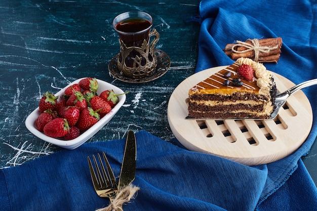 Een plakje chocoladetaart met een glas thee en fruit.