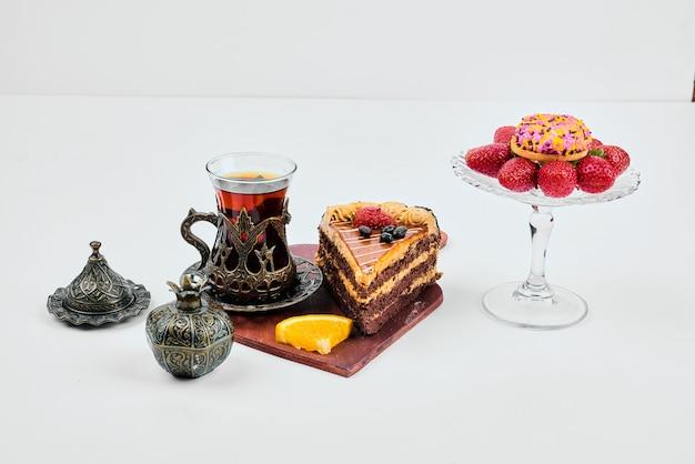 Een plakje chocoladetaart met een glas thee.
