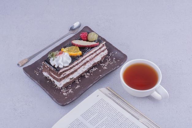 Een plakje chocoladetaart met fruit en een kopje drank.