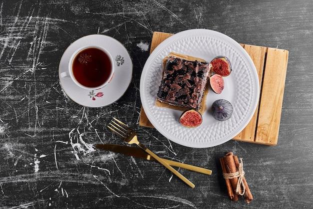 Een plakje chocoladetaart met vijgen en thee in een witte plaat.