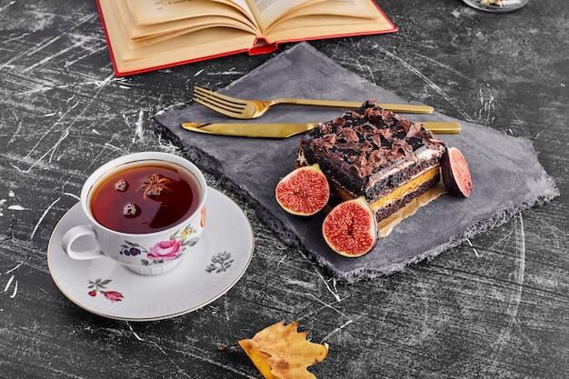 Een plakje chocoladetaart met vijgen en thee op een stenen schaal.