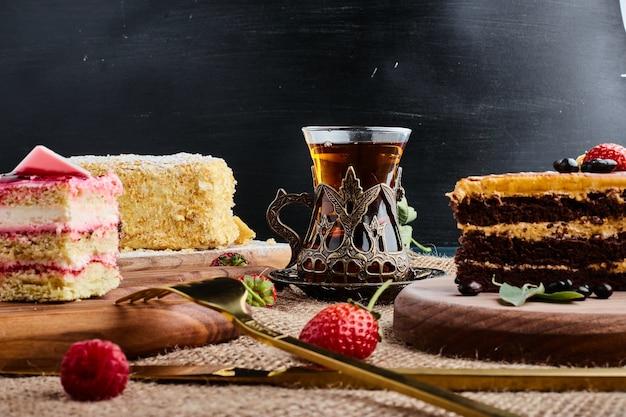 Een plakje chocoladetaart op een houten bord met een glas thee.