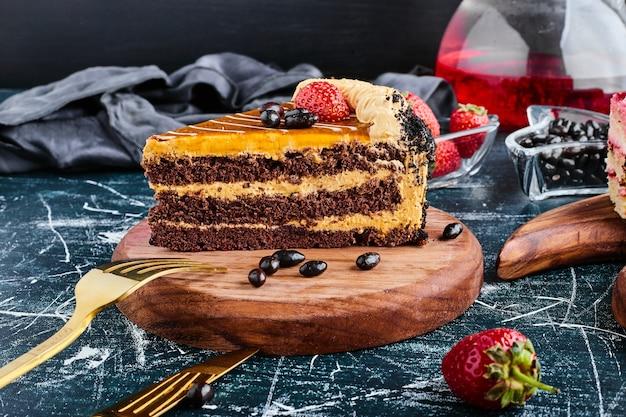 Een plakje chocoladetaart op een houten bord.
