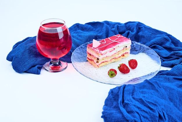 Een plakje frambozencake met een glas wijn.
