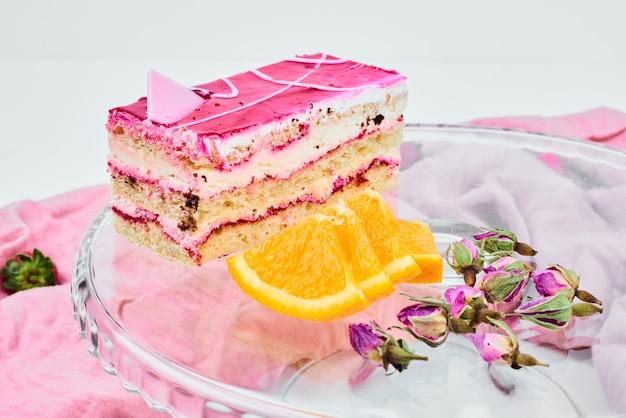 Een plakje frambozencake met sinaasappels.