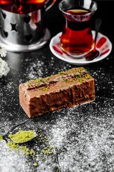 Een plakje geen bakchocoladekaastaart en een glas thee.