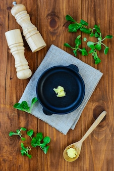 Een plakje ghee boter in een gietijzeren pan met greens en kruiden.