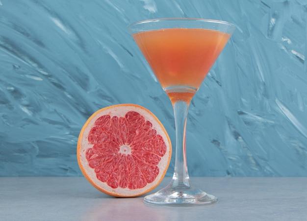 Een plakje grapefruit en sap, op de blauwe achtergrond. hoge kwaliteit foto