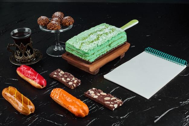 Een plakje groene cake met eclairs en receptenboek.