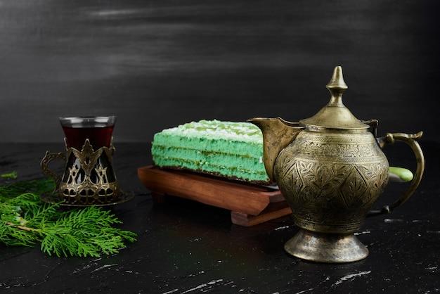 Een plakje groene cake met een glas thee.