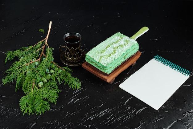 Een plakje groene cake met een receptenboek.