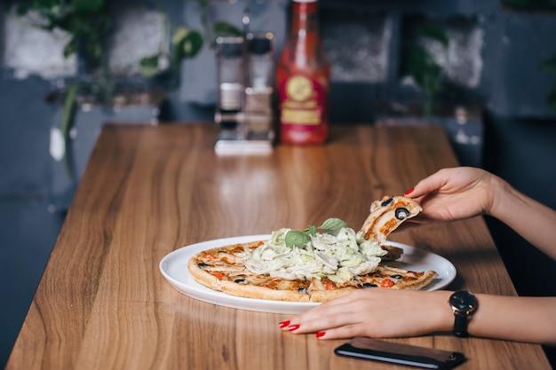 Een plakje grote portie margarita pizza nemen