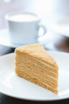 Een plakje honing cake met een kopje melk