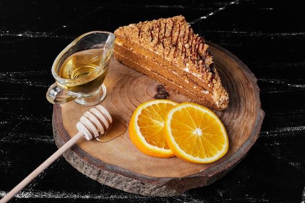 Een plakje honingkoek met stukjes sinaasappel en ahornsiroop