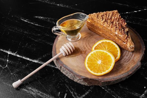 Een plakje honingkoek met stukjes sinaasappel en olie.