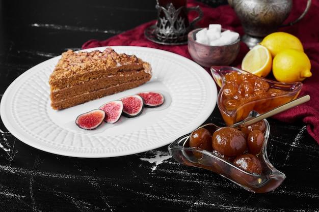 Een plakje honingkoek met vijgen en confituur.