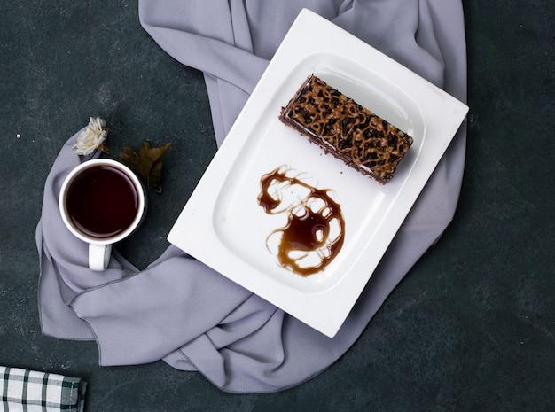 Een plakje karamelcake met gehakte chocolade in witte plaat.