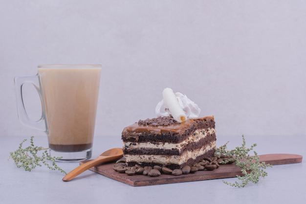 Een plakje karameltaart met een glas cappuccino