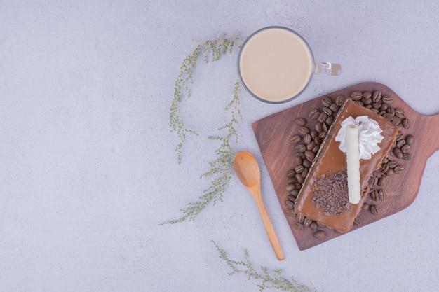 Een plakje karameltaart op een houten schaal met een glas latte
