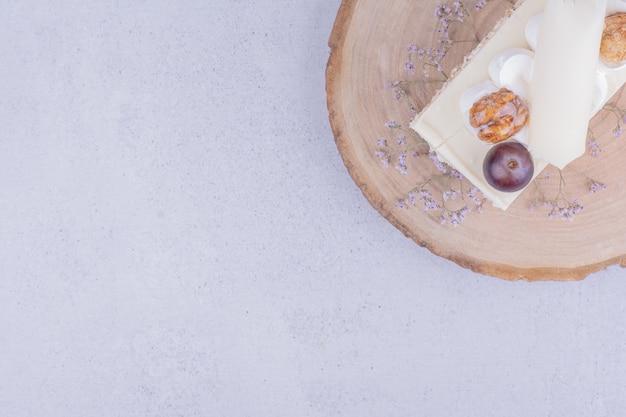 Een plakje kokoscake met druivenmost en walnoot op een houten bord