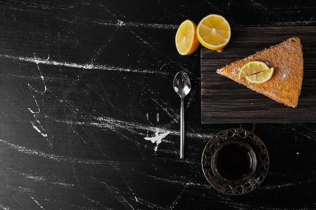 Een plakje medovic cake geserveerd met citroen en thee.