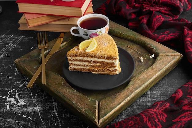 Een plakje medovic cake met citroen en thee.