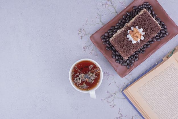 Een plakje medovic cake met gehakte chocolade in een schaal met een kopje kruidenthee