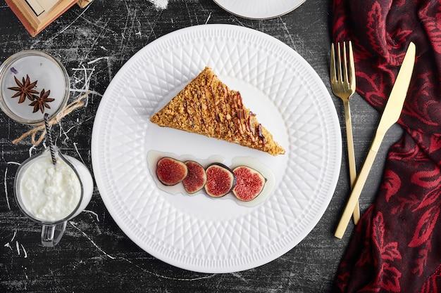 Een plakje medovic cake met vijgen, bovenaanzicht.