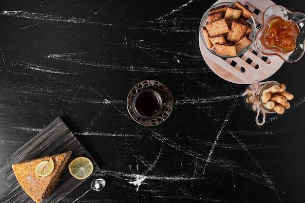 Een plakje medovic cake op zwarte steen geserveerd met confituur en thee.