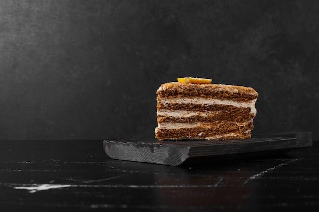 Een plakje medovic cake op zwarte steen.