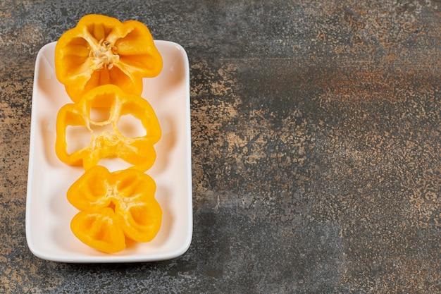 Een plakje peper op de plaat op het marmeren oppervlak