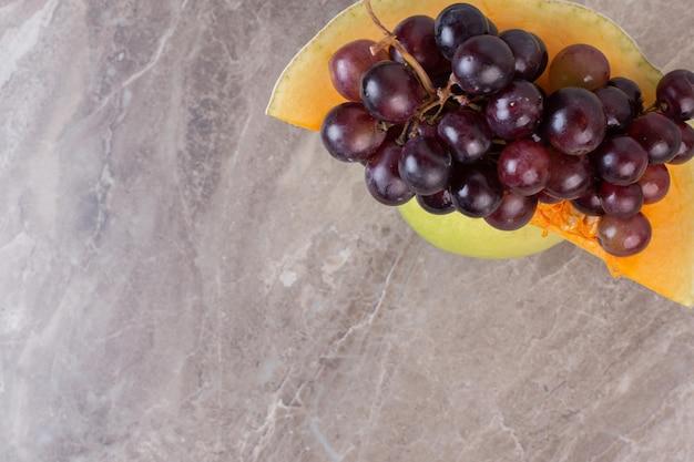 Een plakje pompoen en druiven op marmeren oppervlak.