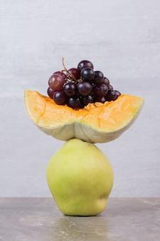Een plakje pompoen, kweepeer en druiven op marmeren tafel.