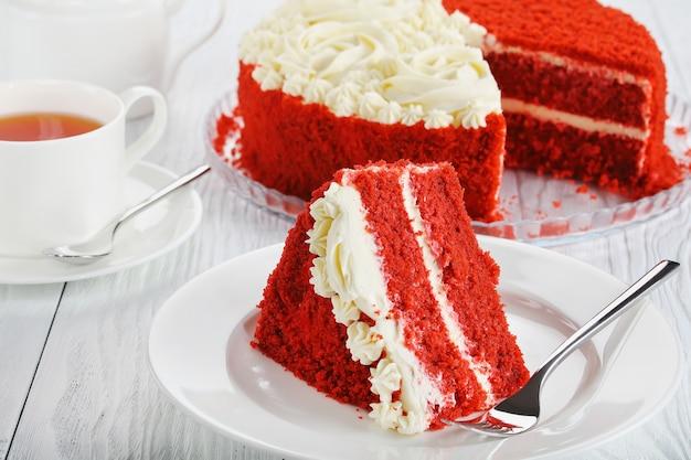 Een plakje rood fluwelen cake gegarneerd met mooie romige rozen op een witte schotel